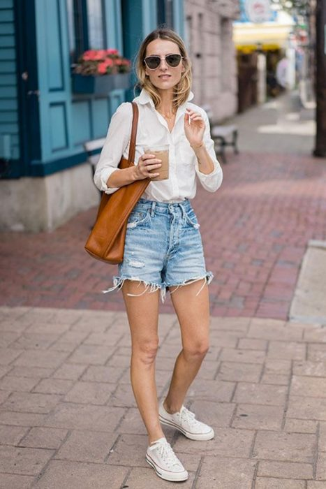 blonde girl with sunglasses, white button-down shirt, denim shorts, white tennis shoes, leather bag and a glass of coffee