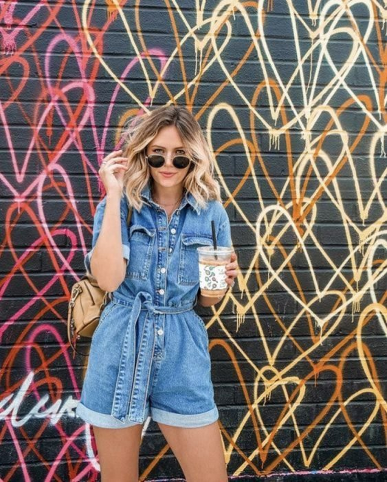 light-haired girl in sunglasses, denim playsuit and leather bag, posing in front of a wall with graffiti