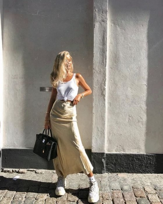 blonde girl in white tank top, pastel yellow satin midi skirt and trainers, black leather bag