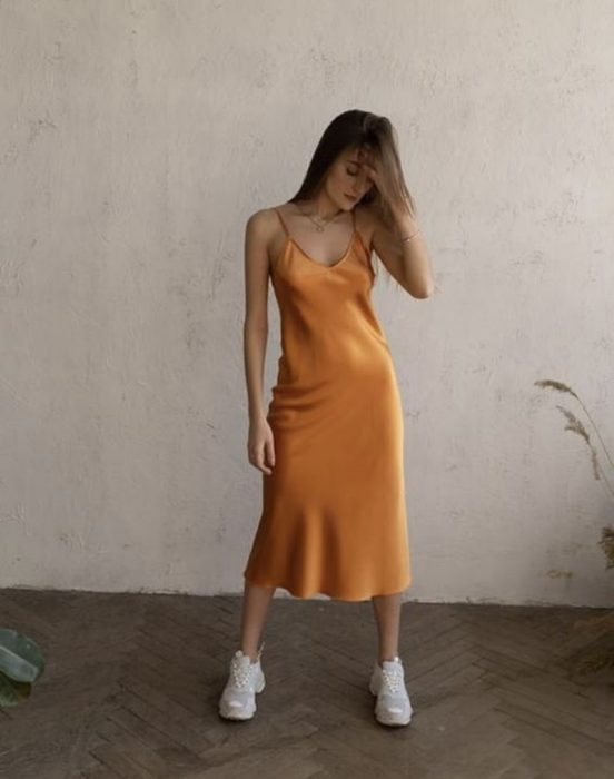 brown haired girl wearing orange satin slip dress with white trainers
