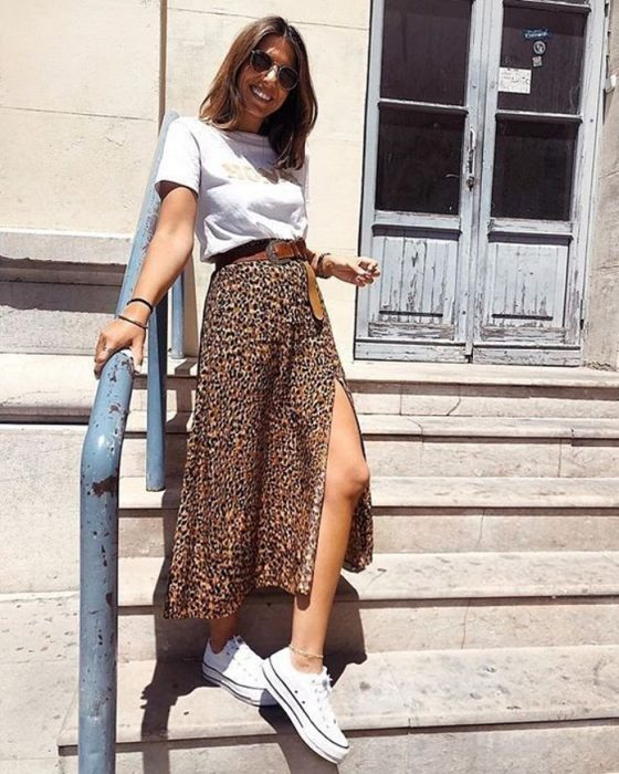 girl with white t-shirt, midi skirt with animal print and sports tennis shoes, brown hair