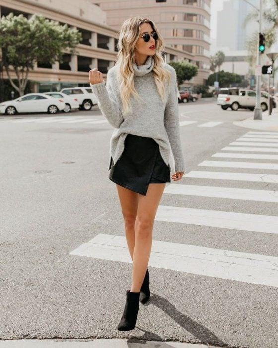 chica con skort de piel, suéter y botas de cuero
