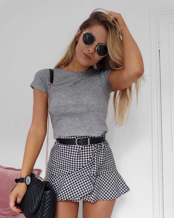 chica con playera gris, cinturón y skort de cuadros