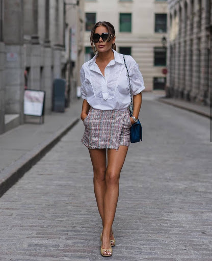 chica con camisa a botones, falda a cuadros y lentes de sol