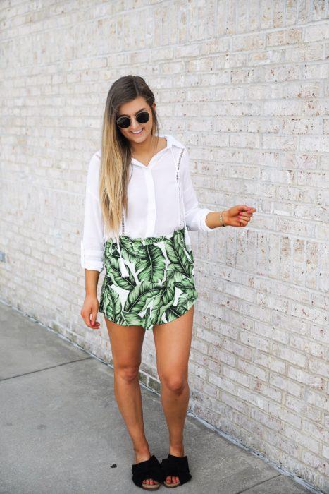 chica con falda verde estampada, lentes de sol y camisa blanca