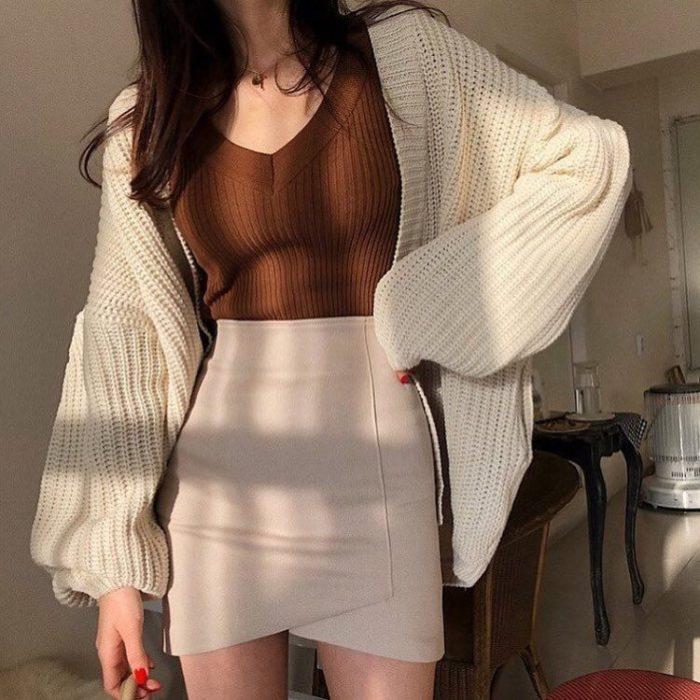 chica con falda beige, blusa cafe y suéter tejido