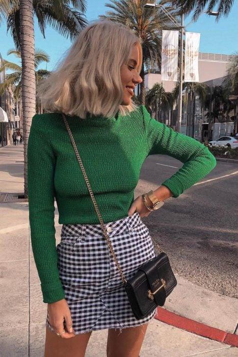 chica con suéter verde y skort a cuadros