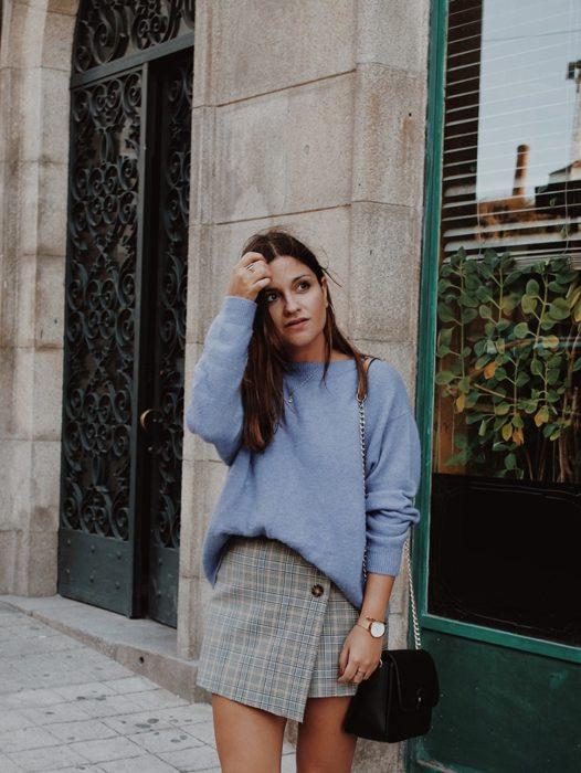 chica con falda gris y suéter azul