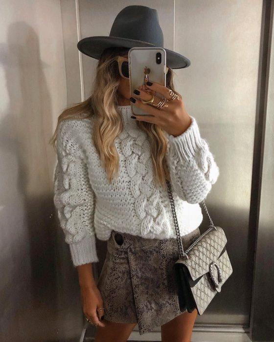 chica con sueter y skort, sombrero y bolso