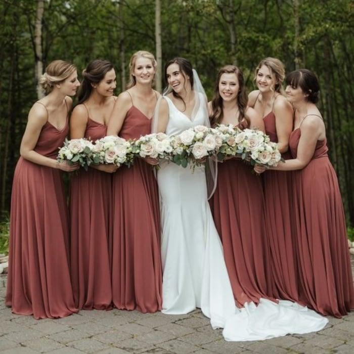vestidos de dama de honor en color granada posando con la novia en un bosque con flores