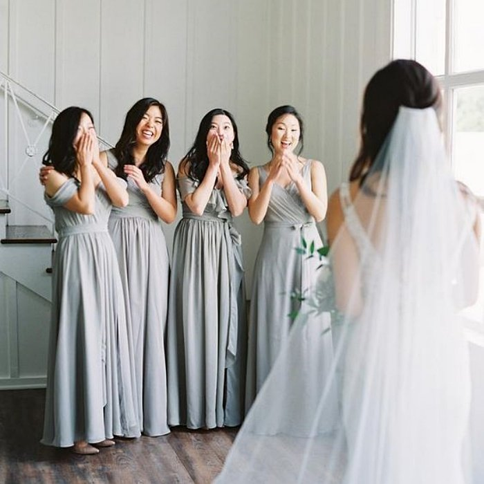 bridesmaids watching the bride, wearing pastel gray dresses