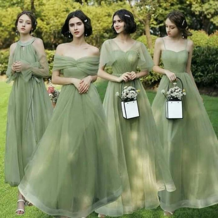 bridesmaids in pastel green dresses carrying bags with flowers