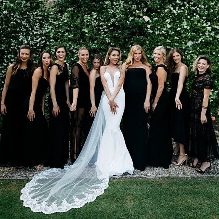 bridesmaids posing with the bride, wearing black dresses in different designs
