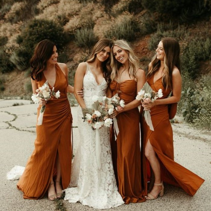 bride with her bridesmaids, in long copper-colored dresses