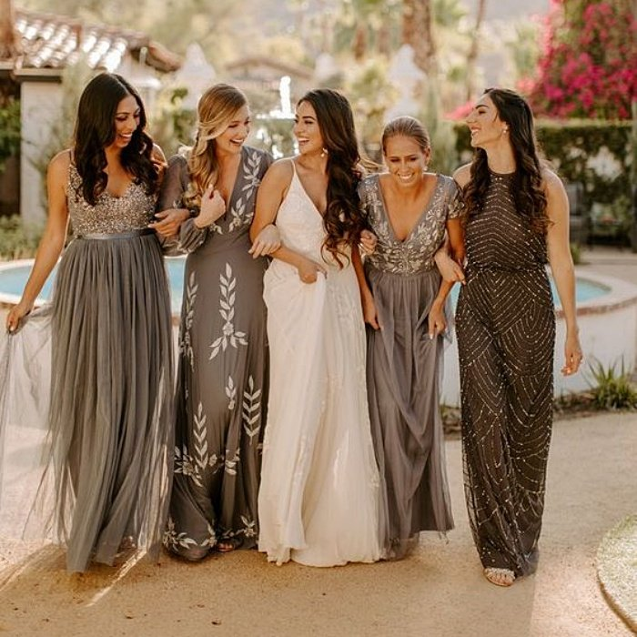 bride with her bridesmaids, wearing gray dresses with different designs