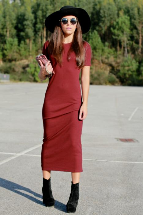 Chica usando un vestido canale, con botines y sombrero y lentes de sol