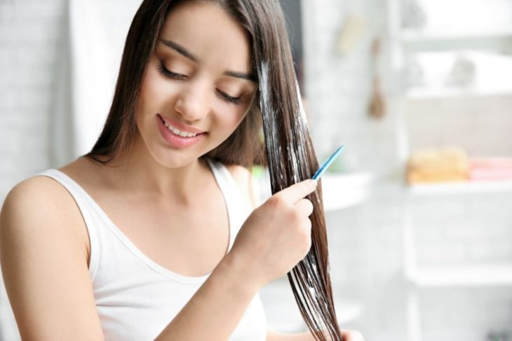 Girl applying hair mask on her wet hair