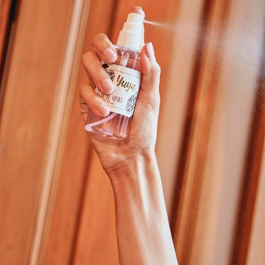 Mano de mujer presionando el atomizador de un frasco con agua de rosas