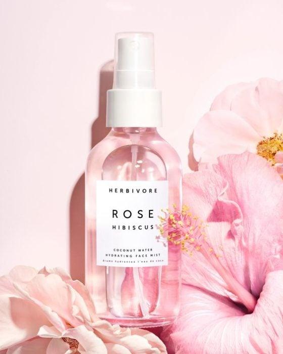 Frasco con agua de rosas en el interior