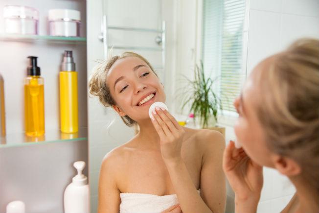 Chica frente al espejo sonriendo y limpiando su rostro con una almohadilla de algodón