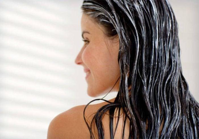 Chica de perfil lavando su cabello largo