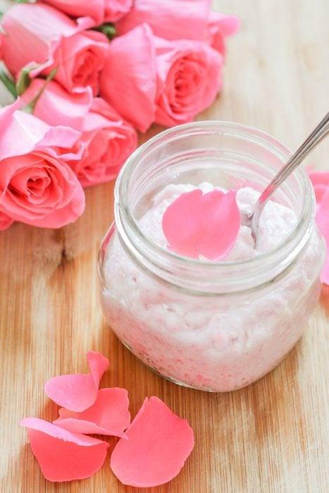 Frasco de cristal con crem hidratante y pétalos de rosas