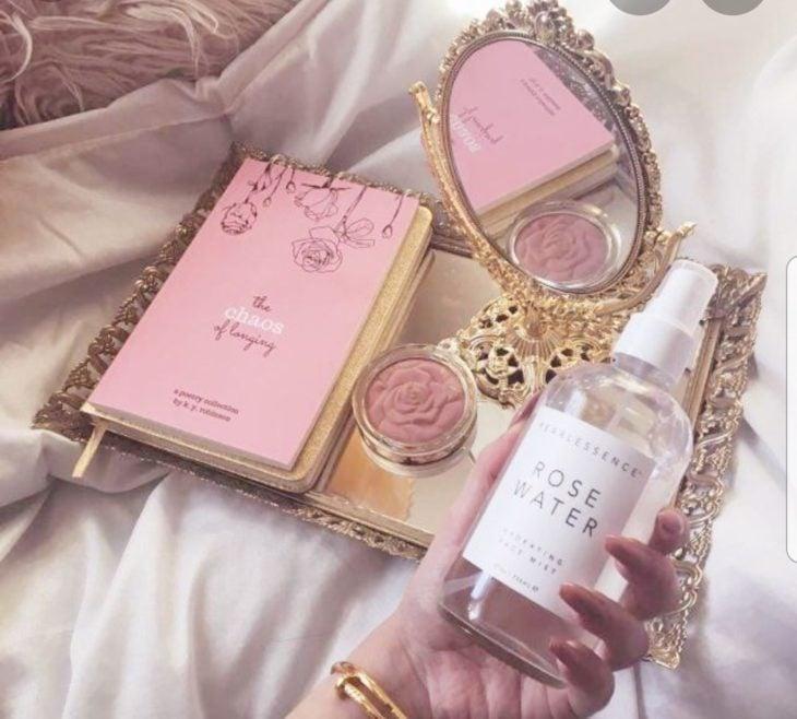 Frasco de plástico con agua de rosas sobre una sábana blanco junto a un espejo pequeño