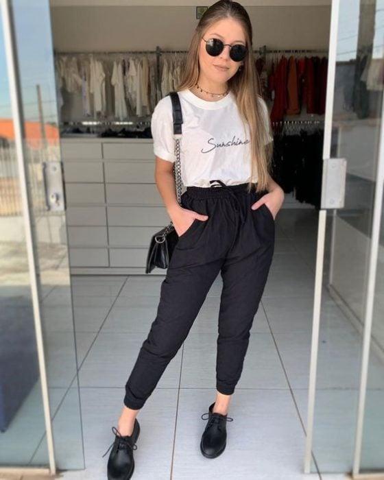 Chica usando jogger negro, zapatos negros y playera blanca