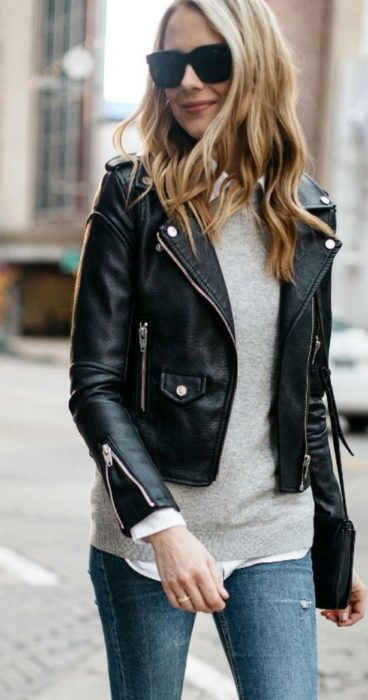 Girl wearing cream sweater, jeans, sunglasses and biker jacket