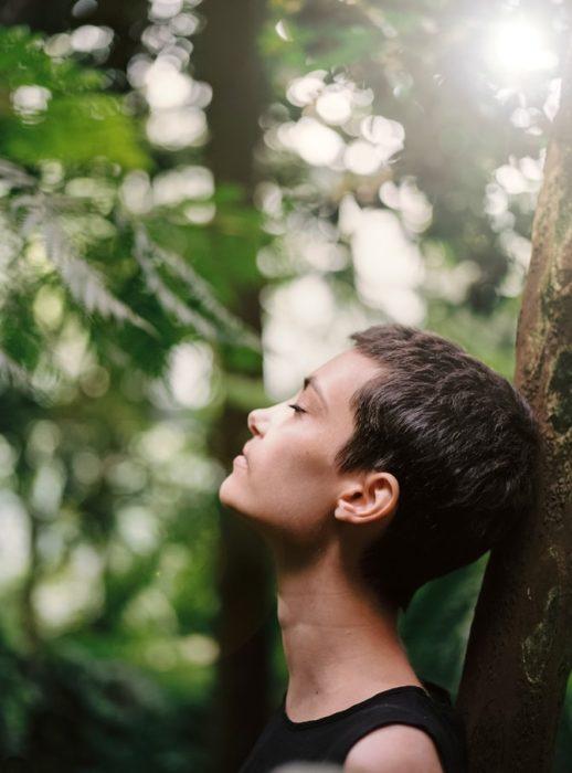 Mujer recargada en un árbol respirando profundo