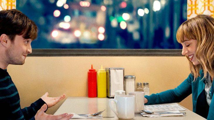 Daniel Radcliffe en la película sentado en una cafetería junto a una chica