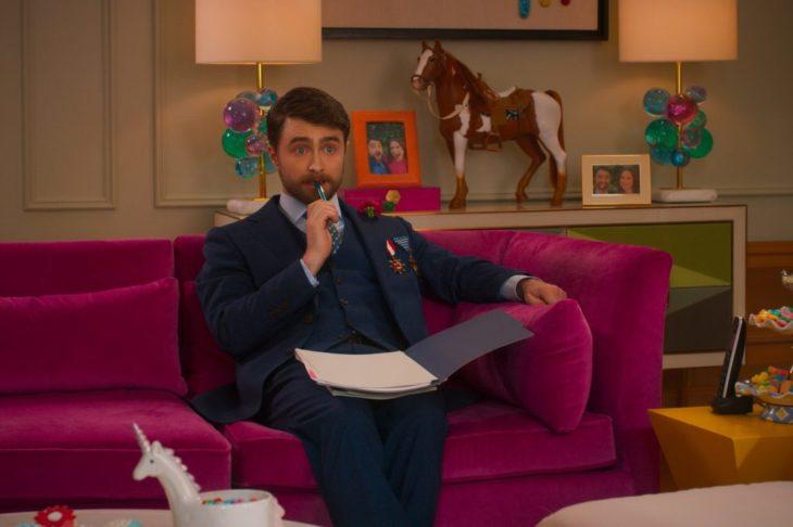 Daniel Radcliffe en la película Unbreakable Kimmy Schmidt: Kimmy contra el reverendo, sentado en un sofá rosa