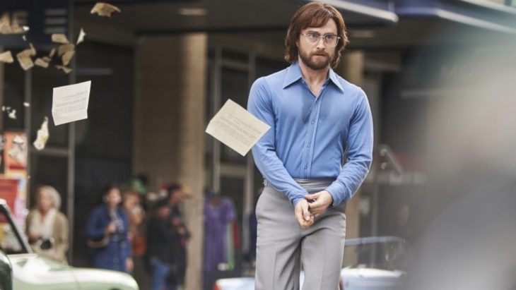 Daniel Radcliffe en la película Escape de Petroria caminando discretamente entre la calle ambientada en los años 70