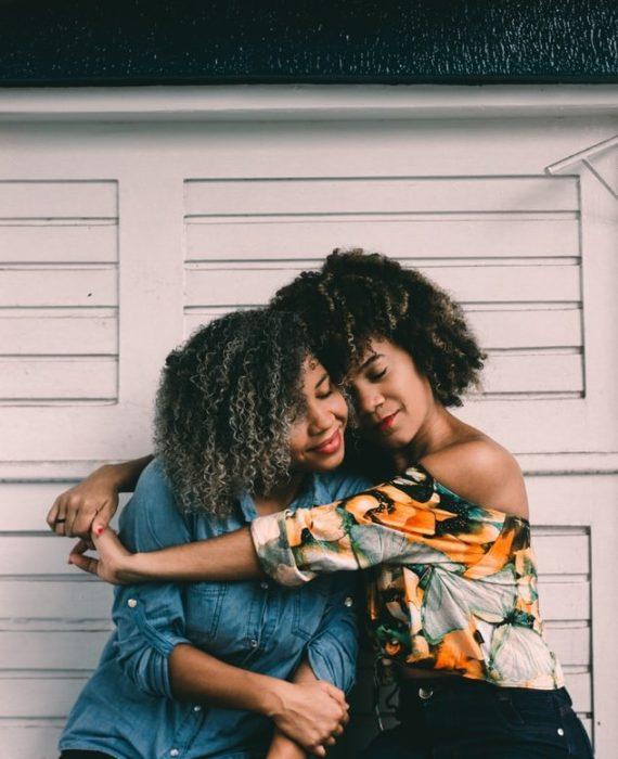 Chicas de cabello rizado estilo afro abrazadas y sonriendo