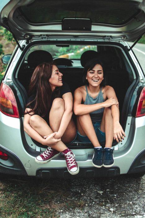 Amigas dentro de un coche sonriendo y charlando