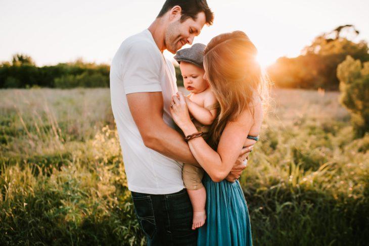 Familia abrazada en un campo de trigo, mujer y hombre sosteniendo a un bebé