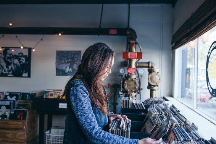 Chica buscando un disco en una tienda antigua