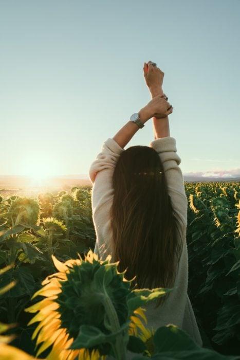 Chica de espaldas mirando un campo de girasoles