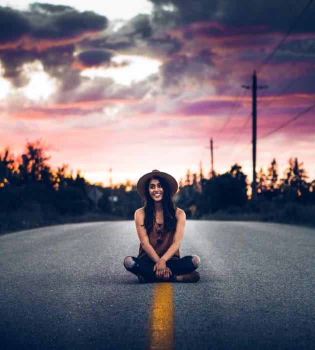 Chica sentada a mitad de carretera llevando gorro negro, jeans y camisa de tirantes