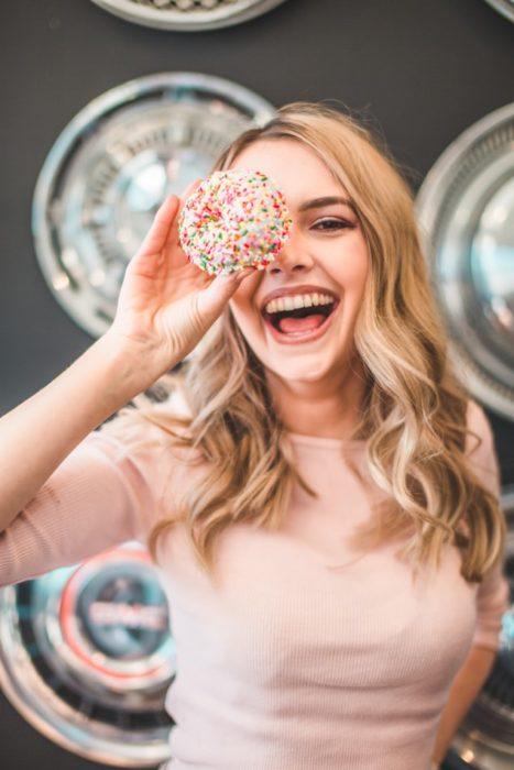 Chica sonriendo y jugando con una rosquilla
