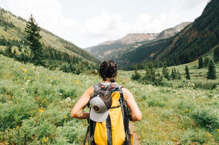 Chica volteada de espaldas llevando una mochila de camping color amarilla y mirando un bosque frondoso