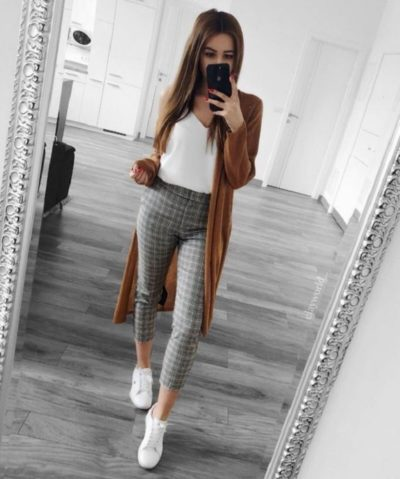 Girl wearing white T-shirt, long brown sweater and black and white print leggings