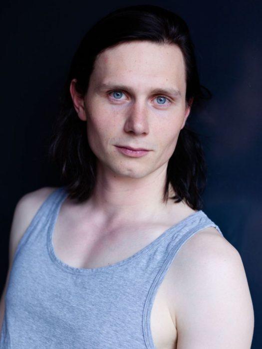 Moritz Jahn, actor alemán en la serie Dark, llevando camisa de tirantes en tono azul