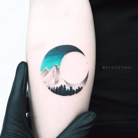 Tattoo of a crescent with an interior landscape of the mountains