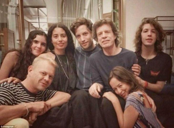 Mick Jagger junto a sus seis hijos sentado en un sofá