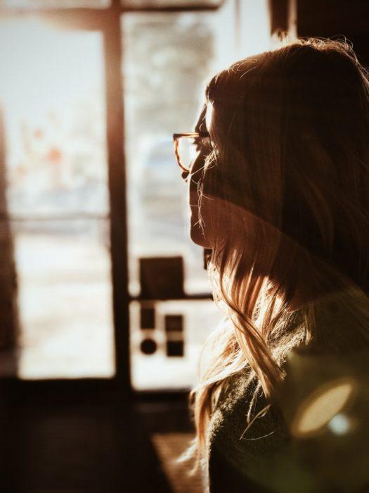 Chica usando lentes con luz del sol sobre su rostro