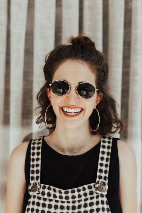 Chica sonriéndo usando gafas de sol