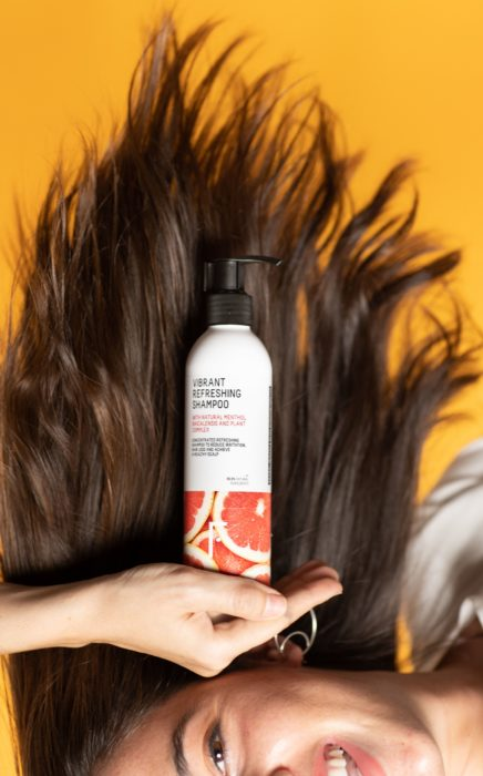 Botella de champú sobre el cabello
