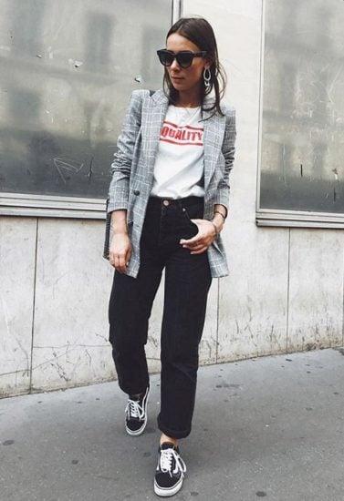 Chica usnado vans, jeans negros, playera blanca y blazer gris