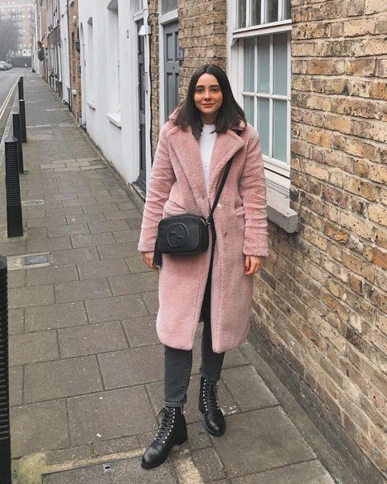 Olivia Jackson usando jeans, botines y un abrigo de peluchito color rosa palo